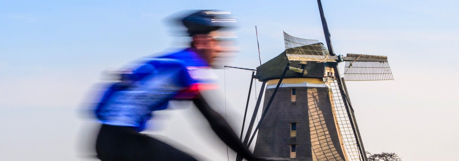 Cycling_past_windmill_Amsterdam.jpg